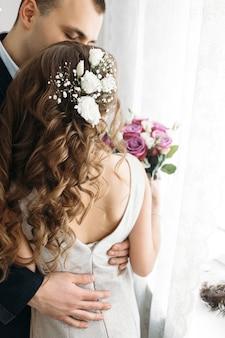 A linda noiva e o noivo abraçando no quarto