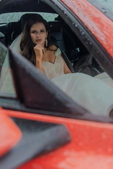 A linda noiva está sentada em um carro vermelho em um vestido branco e com um buquê. conceito de casamento