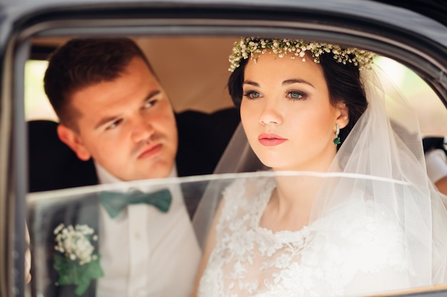 A linda noiva está sentada no carro olhando pela janela