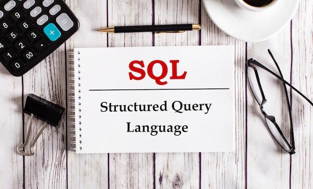 A linguagem sql structured query é escrita em um bloco de notas branco perto de uma calculadora