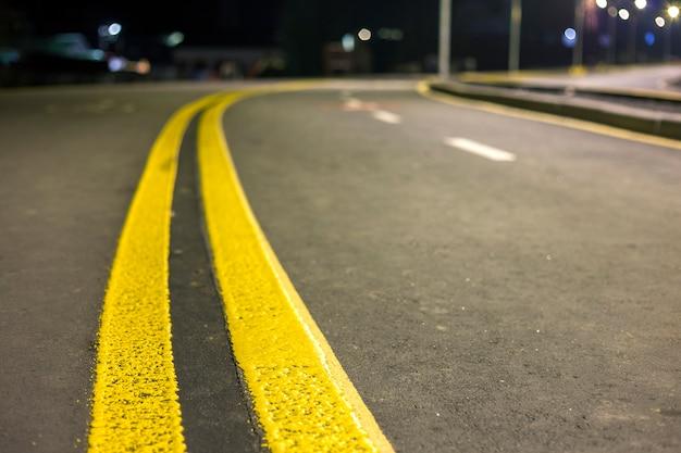 A linha amarela brilhante larga do sinal da marcação de rua ao longo da estrada de asfalto vazia lisa larga moderna que estica ao horizonte.