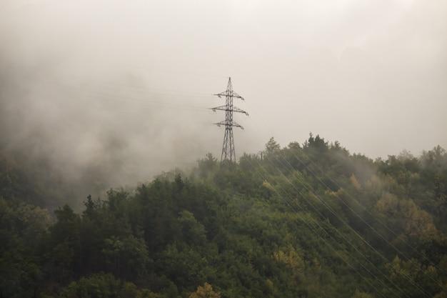 A linha de energia é alta nas montanhas no meio do nevoeiro