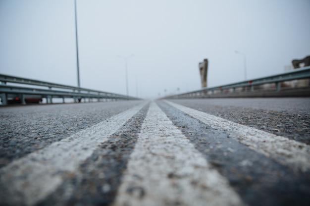 A linha divisória na estrada é branca a vista de baixo na estrada pavimentada indo