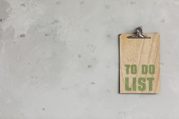 A lista de tarefas a completar em uma placa de madeira está pendurada em uma parede de concreto