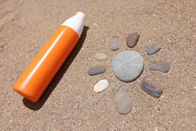 A loção de proteção solar repousa na areia quente ao lado da figura do sol feita de pedras
