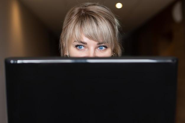 A loira linda e feliz nas mãos de um laptop
