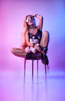 A loira sexy de cabelos longos brinca com um ursinho de brinquedo em acessórios bdsm e um chicote
