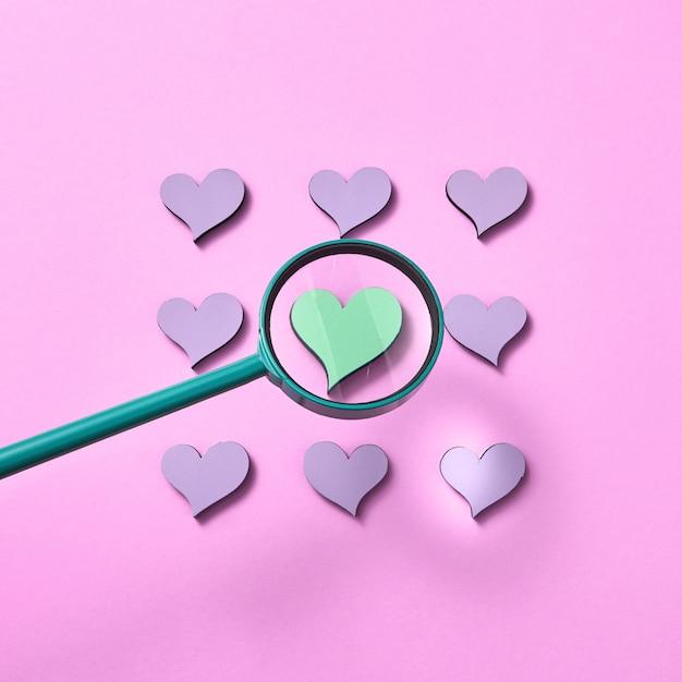 A lupa grande está aumentando o tamanho do coração verde ao redor de outros corações cor de lavanda