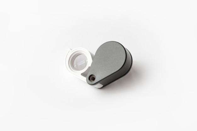 A lupa para diamantes ou considera o amuleto isolado em um fundo branco.