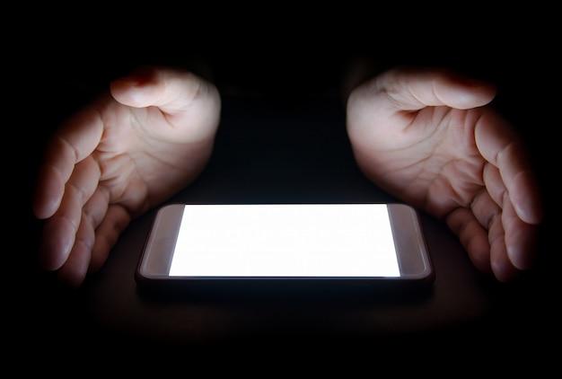 A luz branca do smartphone reflete sua mão à noite no escuro