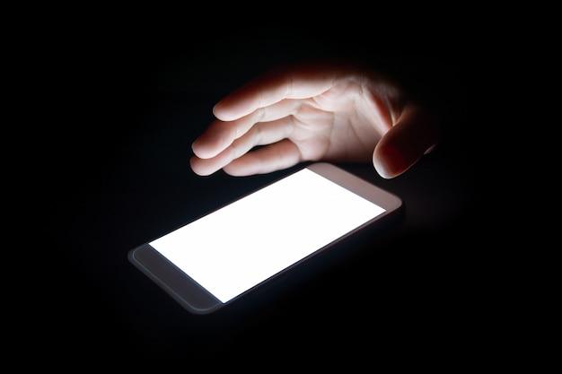 A luz branca do smartphone reflete sua mão