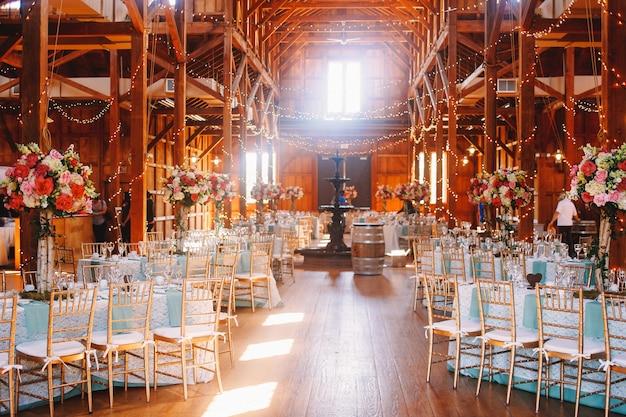A luz branca ilumina um hangar de madeira preparado para um casamento