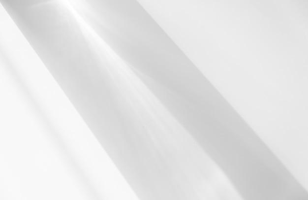 A luz brilha no fundo branco fotografando as linhas de sombra da cortina