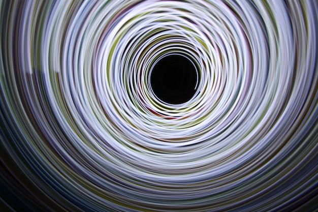 A luz da cor do arco-íris se move em uma filmagem de longa exposição no escuro.