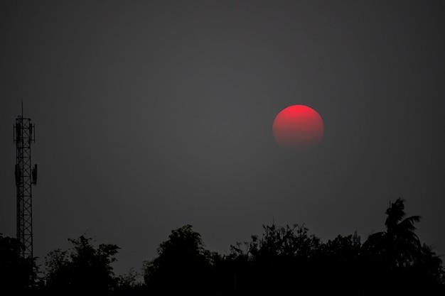 A luz do por do sol da noite é alaranjada após a antena e as árvores do receptor de telefone.