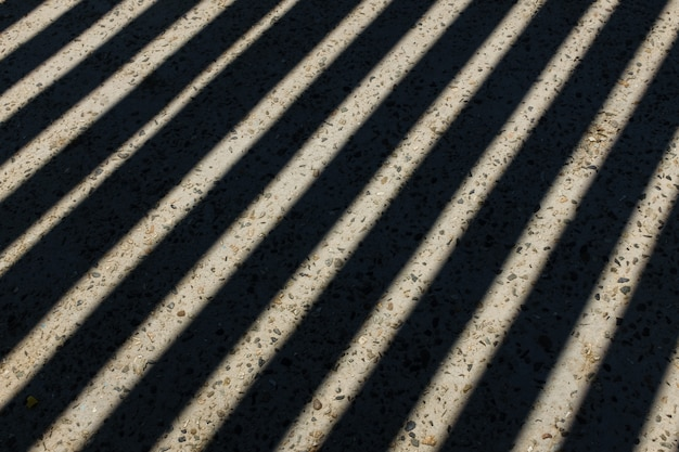 A luz do sol brilha através da cerca de madeira e faz sombras de listras geométricas no chão. sombras de cerca de madeira no chão. textura de sombras de vedação