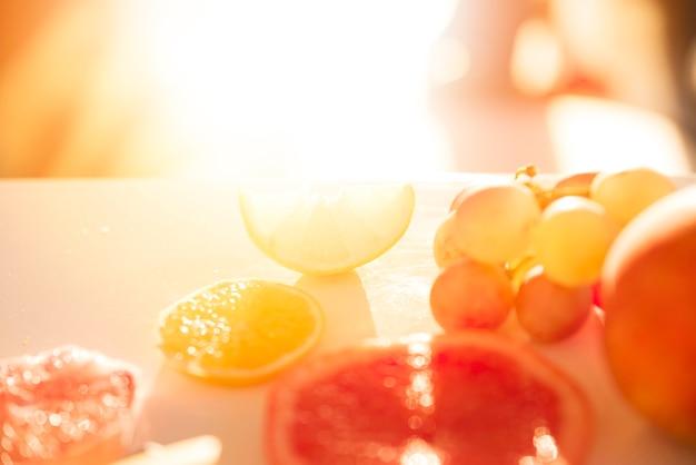 A luz do sol caindo sobre as fatias de limão; laranja; toranja e uvas na superfície