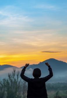 A luz do sol da manhã embaçada atrás das montanhas e as mulheres levantam seus braços.