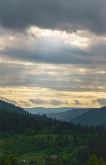 A luz do sol irradia através das nuvens na cadeia de montanhas dos cárpatos na ucrânia