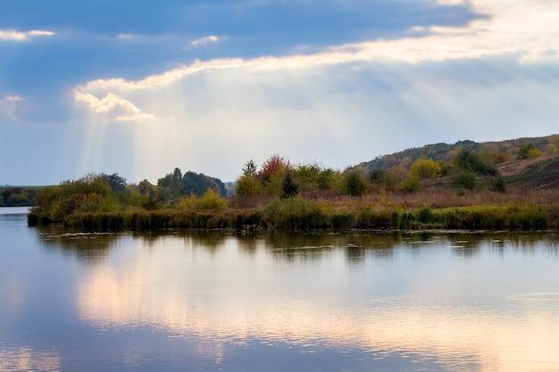 A luz do sol penetra pelas nuvens sobre o rio e a floresta ao pôr do sol. as nuvens são refletidas na água do rio.