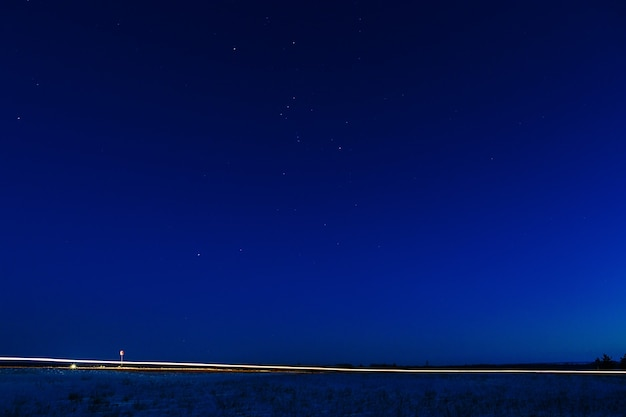 A luz dos faróis de um carro em um fundo do céu estrelado.