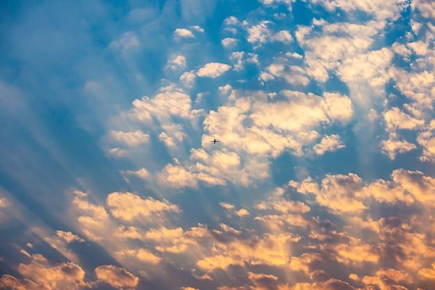 A luz dourada do sol e o avião no céu.