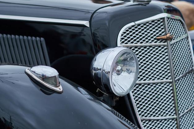 A luz frontal de um velho carro preto