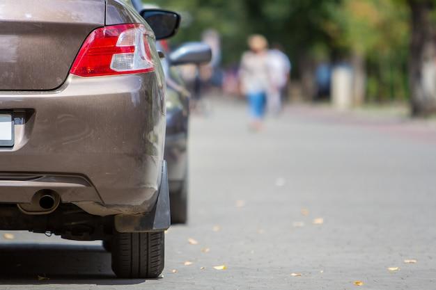 A luz traseira de um carro estacionou perto do meio-fio na lateral da rua em um estacionamento.