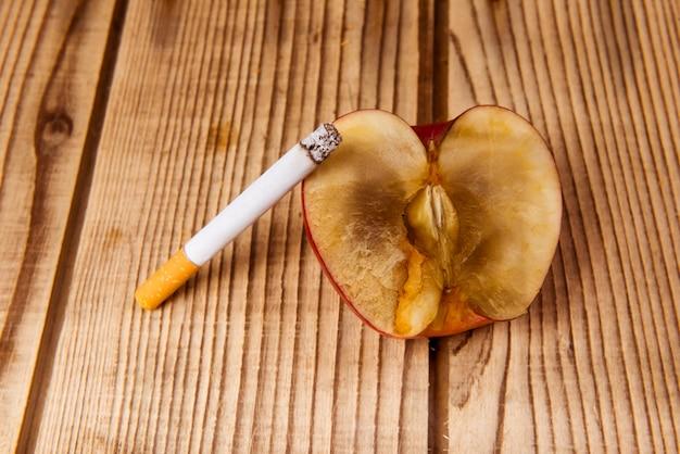 A maçã murcha e os cigarros representam uma má influência.