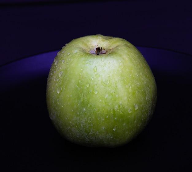 A maçã suculenta verde com água deixa cair na placa preta no fundo escuro.