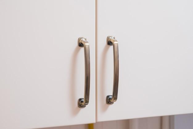A maçaneta de metal da porta do armário da cozinha.