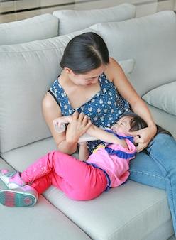 A mãe abraça sua menina da criança que bebe de uma garrafa no sofá.
