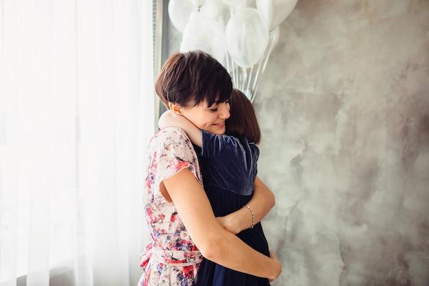 A mãe abraçando sua filha no quarto
