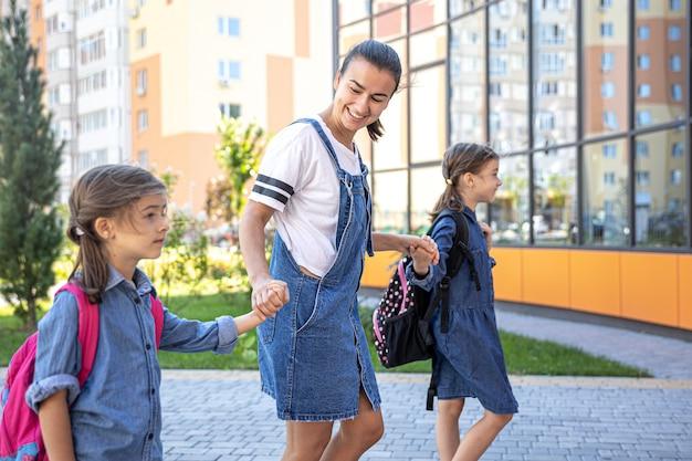A mãe acompanha os alunos à escola, as crianças com mochilas escolares vão à escola.