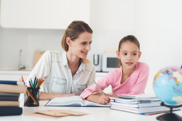 A mãe ajuda a filha a fazer o dever de casa na cozinha.