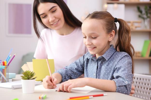 A mãe ajuda a menina a fazer o dever de casa, filhos e pais