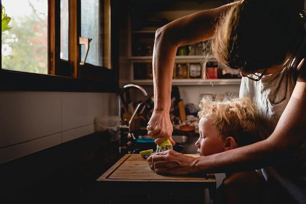 A mãe ajudou o filho a espremer frutas.