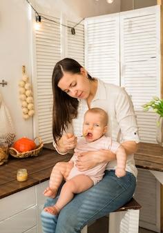 A mãe alimenta a filha com uma colher na cozinha. a primeira isca
