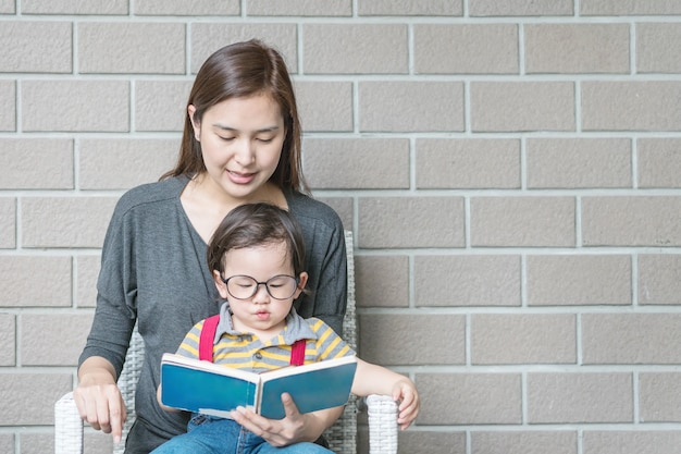 A mãe asiática do close up está ensinando seu filho a ler um livro no fundo textured parede de tijolo de pedra com espaço da cópia