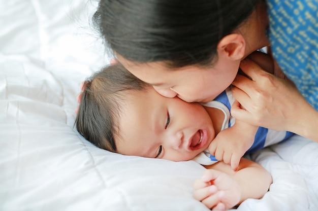 A mãe asiática está jogando e está beijando seu bebê pequeno na cama.