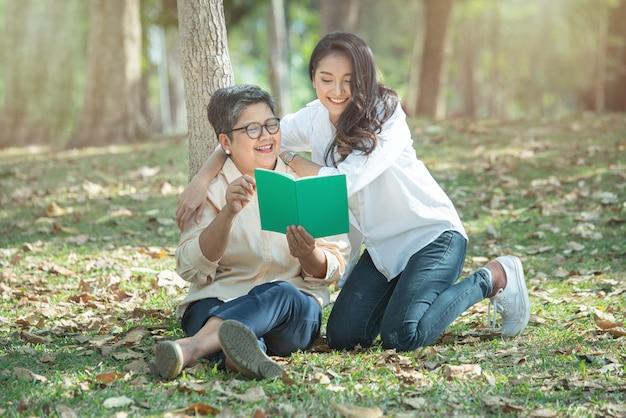 A mãe asiática mais velha e a filha que leem um livro nas madeiras no gramado da grama verde, o conceito de uma vida familiar feliz e de relações familiares, vida da aposentadoria têm o estilo de vida das férias.