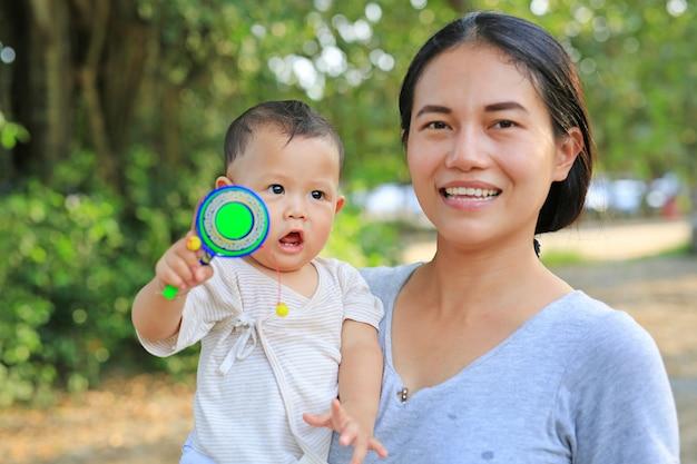 A mãe asiática nova que leva seu bebê e que joga pongapaeng brinca (brinquedo chinês) fora.