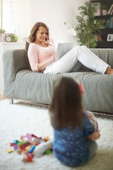 A mãe assiste ao vídeo em um tablet enquanto a filha brinca com brinquedos no tapete