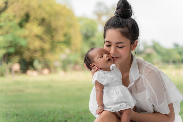 A mãe bonita nova asiática que guarda seu recém-nascido está dormindo e sente com amor