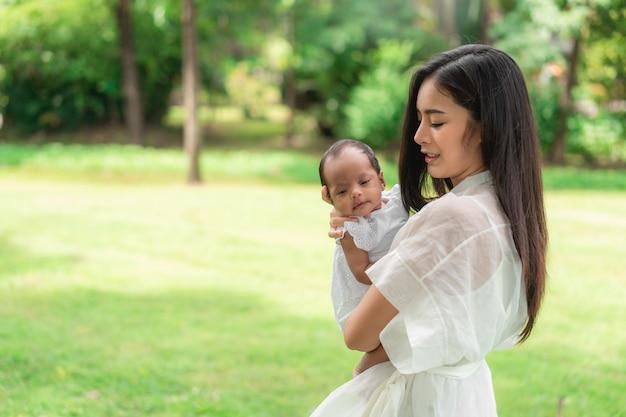 A mãe bonita nova asiática que guarda seu recém-nascido está dormindo e sente-se com amor e tocando-se delicadamente então sentando-se na grama verde no parque