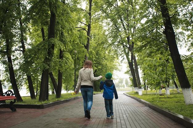 A mãe caminha com o filho no verão, caminha com a família, tradições familiares, amor e compreensão