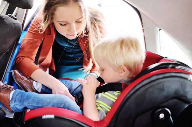 A mãe coloca a criança no assento do carro e aperta os cintos de segurança.