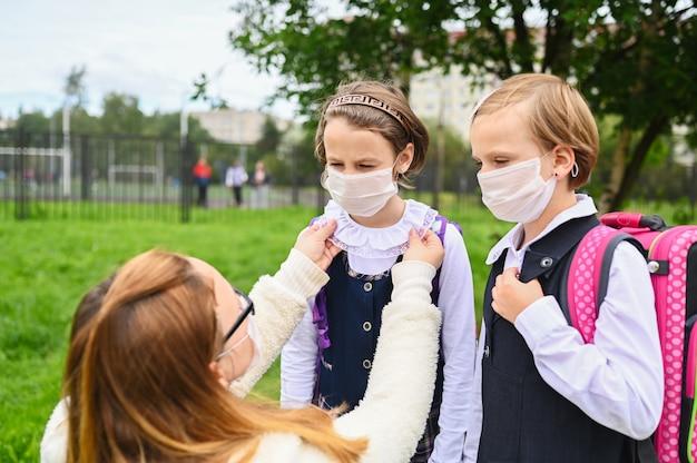 A mãe coloca uma máscara de segurança no rosto da filha. estudantes prontas vão para a escola.