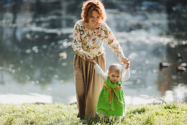 A mãe com a filha que anda perto do lago