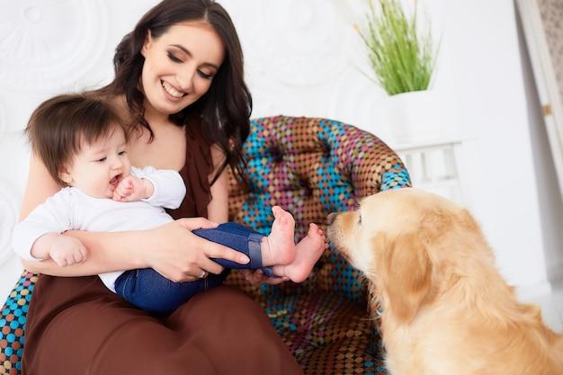 A mãe com a filha sentada na cadeira perto do cão